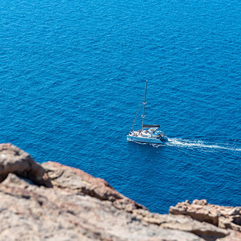 Boot vor den steilen Klippen auf Santorin