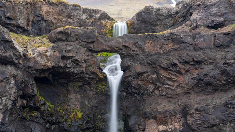 Wasserfall mit Felsbogen in Island