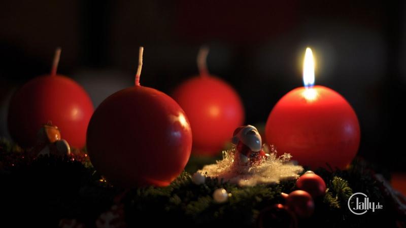 Adventskranz am ersten Advent mit brennender Kerze